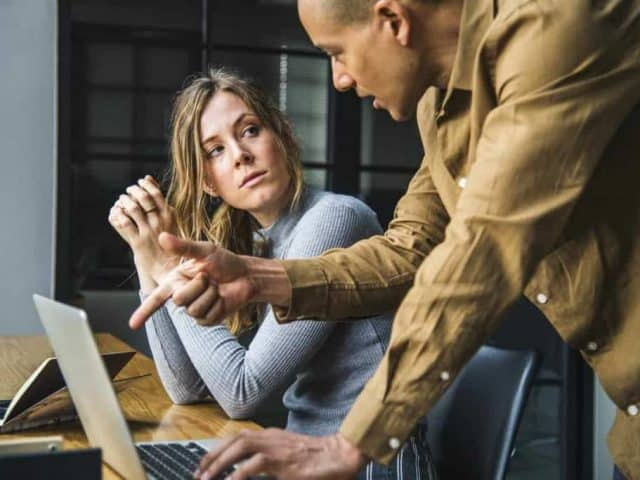 A man explaining a Proprietary Email Marketing Software campaign for a sigitial marketing strategy to a female coworker